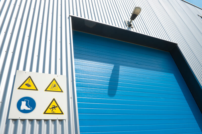 industrial unit with blue roller door and some warning signs